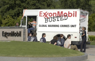 "Greenpeace activists who have chained themself to a Greenpeace vehicle and to the entrance of the Exxon Mobil Headquarters are being observed by a couple of policemen and -women. The vehicle says ""ExxonMobil Busted"" and ""Global Warming Crimes Unit"" on it."